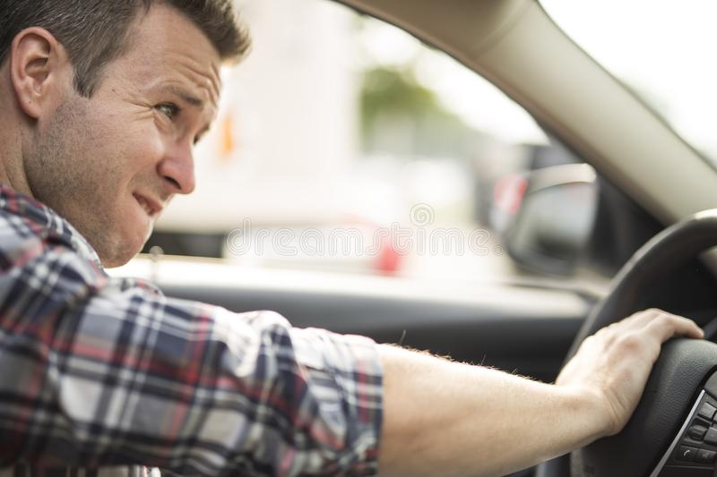 Irritated young man driving a car. Irritated driver. An Irritated young man driving a car stock photo