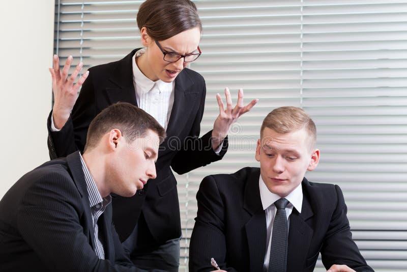 Irriterad affärskvinna på mötet fotografering för bildbyråer