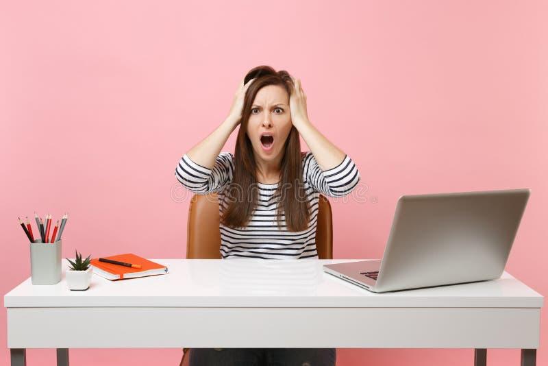 Irriterad kvinna som skriker klamra sig fast intill huvudet för att sitta och arbeta på det vita skrivbordet med moderna den isol arkivfoto