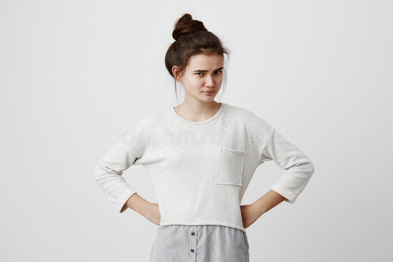 Irriterad och missbelåten brunettflicka med hairbun och den ovala framsidan, mörka ögon, bärande lös tillfällig tröja som rynkar  arkivbild