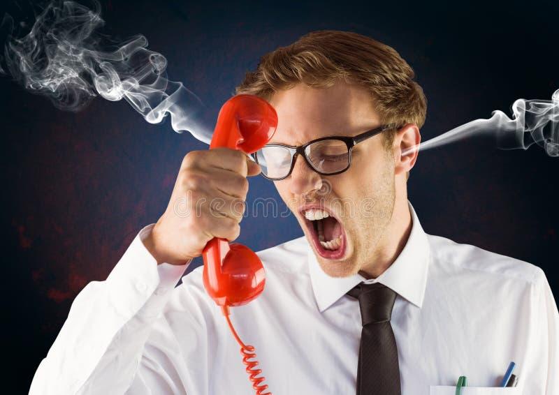 irritez le jeune homme avec la vapeur sur des oreilles criant au téléphone Fond noir et bleu photos libres de droits