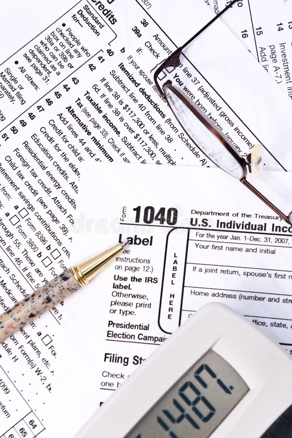 IRS 1040. Image of IRS 1040 tax forms with pen, calculator, and glasses royalty free stock photos