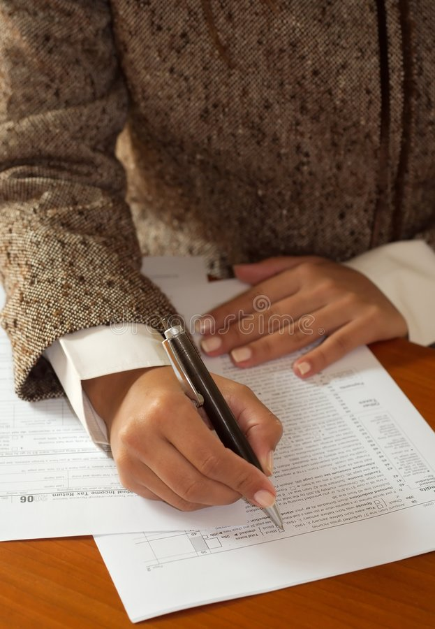 Irs. A woman filling the irs form royalty free stock photography