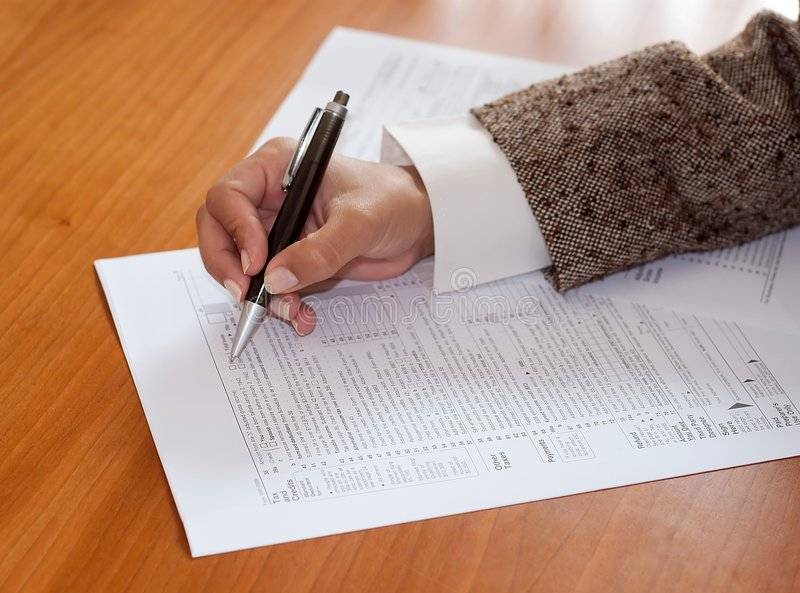 Irs. A woman filling the irs form royalty free stock images