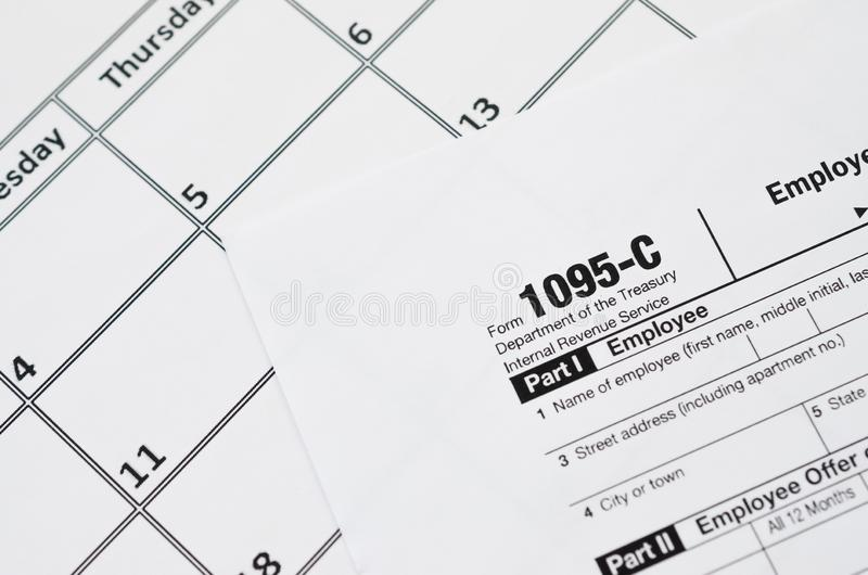 IRS Form 1095-C Employer-Provided Health Insurance Offer and Coverage tax blank lies on empty calendar page. Tax period concept. Copy space for text stock images