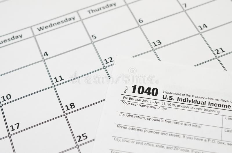 IRS Form 1040 Individual Income Tax Return blank lies on empty calendar page. Tax period concept. Copy space for text stock images