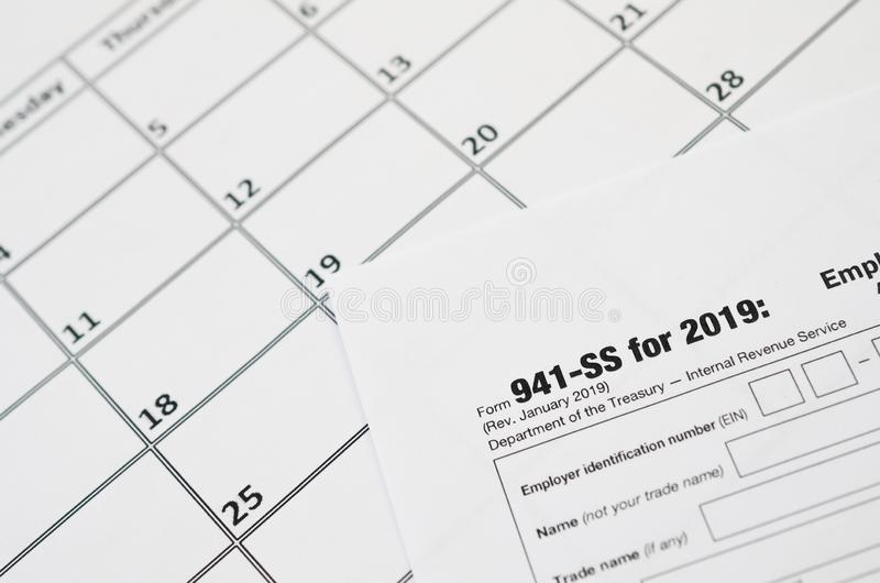 IRS Form 941-SS Employer`s quarterly federal tax return blank lies on empty calendar page. Tax period concept. Copy space for text stock image