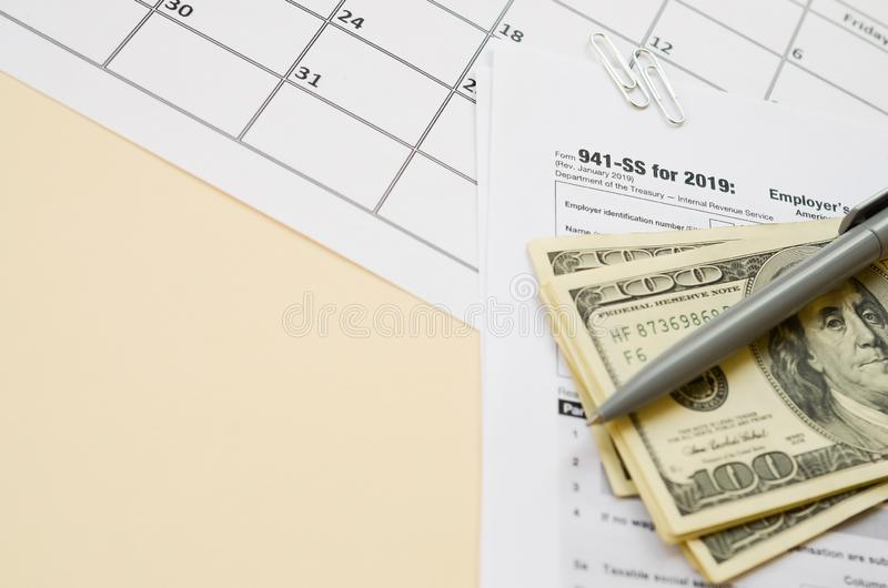 IRS Form 941-SS Employer`s quarterly federal tax return blank lies with pen and many hundred dollar bills on calendar page. Tax period concept. Copy space for stock photography
