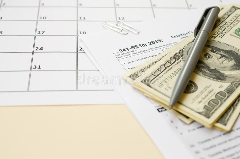 IRS Form 941-SS Employer`s quarterly federal tax return blank lies with pen and many hundred dollar bills on calendar page. Tax period concept. Copy space for stock image