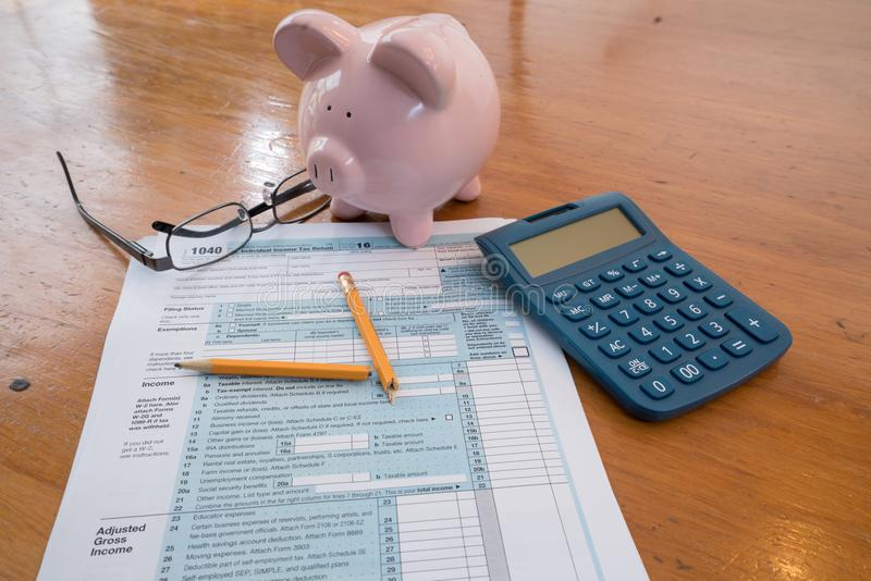IRS Tax Form with Piggy Bank and Calculator Broken Pencil. IRS Tax Form with Piggy Bank, Calculator, Broken Pencil and Glasses royalty free stock photography