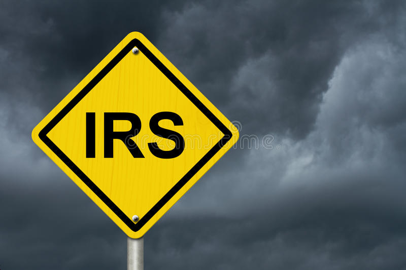 IRS Warning Sign. An American road warning sign with word IRS with a stormy sky background royalty free stock photography