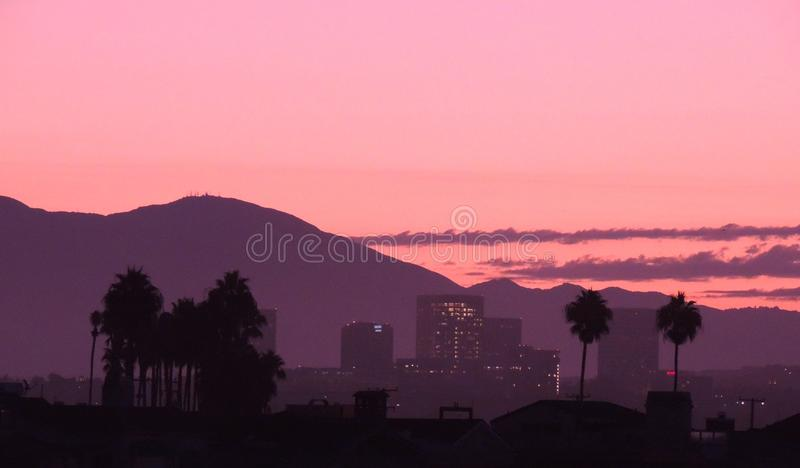 Irvine from Newport Beach California. Tall buildings in Irvine taken from Newport Beach showing palms as silhouettes royalty free stock image