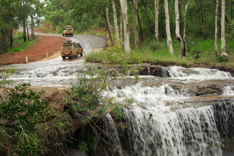 Isabella Falls. Four wheel vehicles coming back from the red dirt tracks of Cape York and crossing the river at Isabella Falls, North Queensland, Australia stock photography