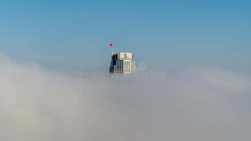 Isbank headquarter skyscraper under heavy fog at Levent Istanbul, Turkey stock photography