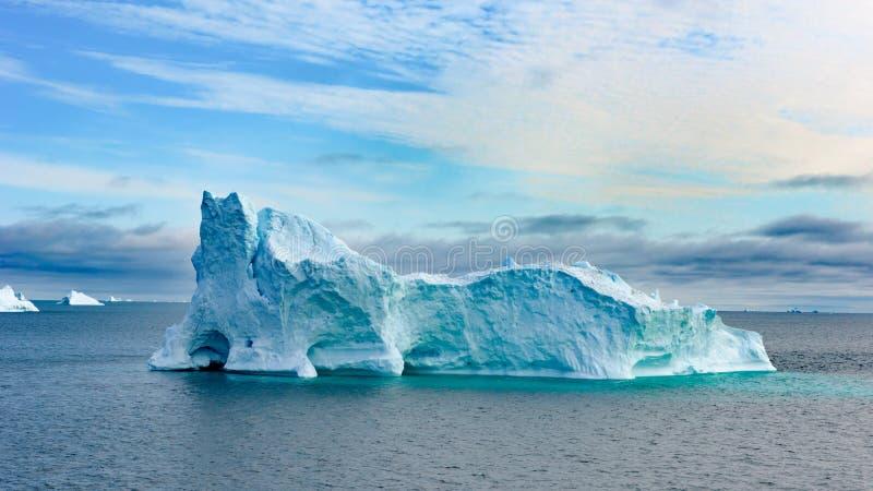 Isberg i Grönland Färgrik enorm isbergbyggnad med tornet och porten arkivbild