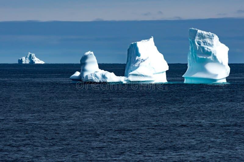 Isberg i solljus som skiner i turkos över mörkt - blått arktiskt hav, Grönland royaltyfri bild