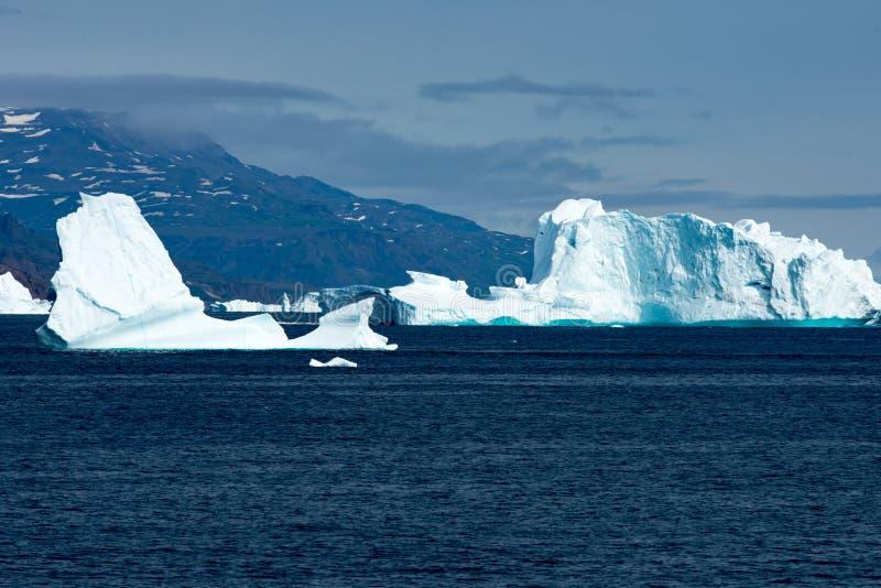 Isberg i solljus som skiner i vit och turkos över mörkt - blått arktiskt hav, Grönland royaltyfria bilder