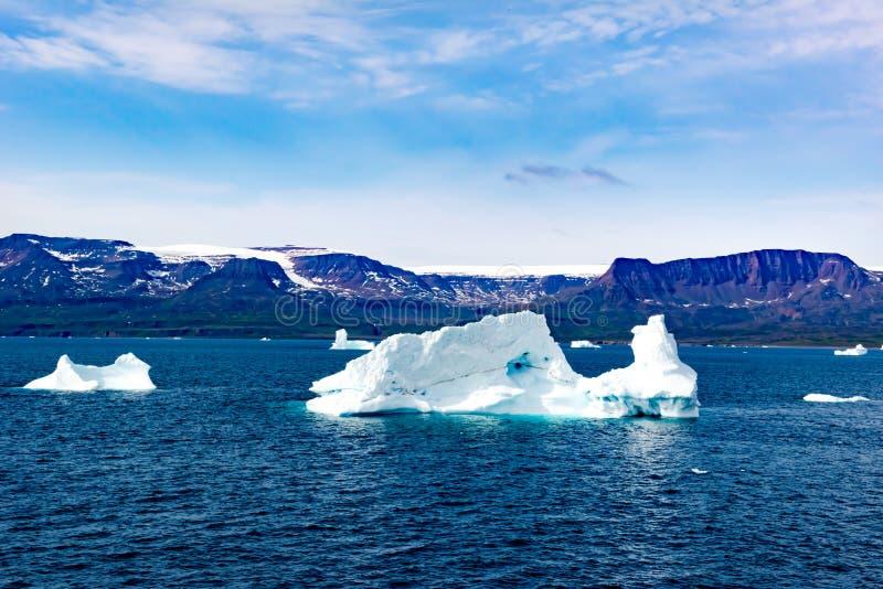 Isberg i solljus som skiner i vit och turkos över mörkt - blått arktiskt hav, Grönland royaltyfria foton