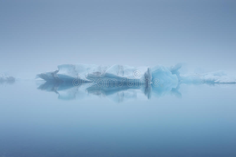 Isberg och deras reflexioner i en dimma, Jokulsarlon, Island arkivfoto