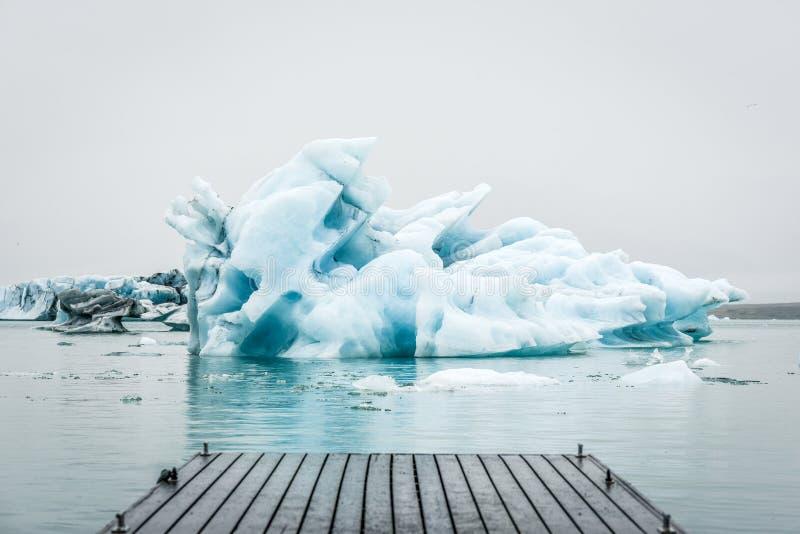 Isberg som svävar i den Jokulsarlon lagun på Island med en br royaltyfria bilder