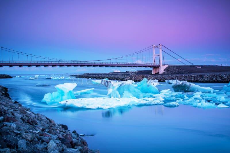 Isbergdelar svävar till havet under en bro i fjärden i den berömda Jokulsarlon islagun i Island Global uppv?rmning, arkivfoto