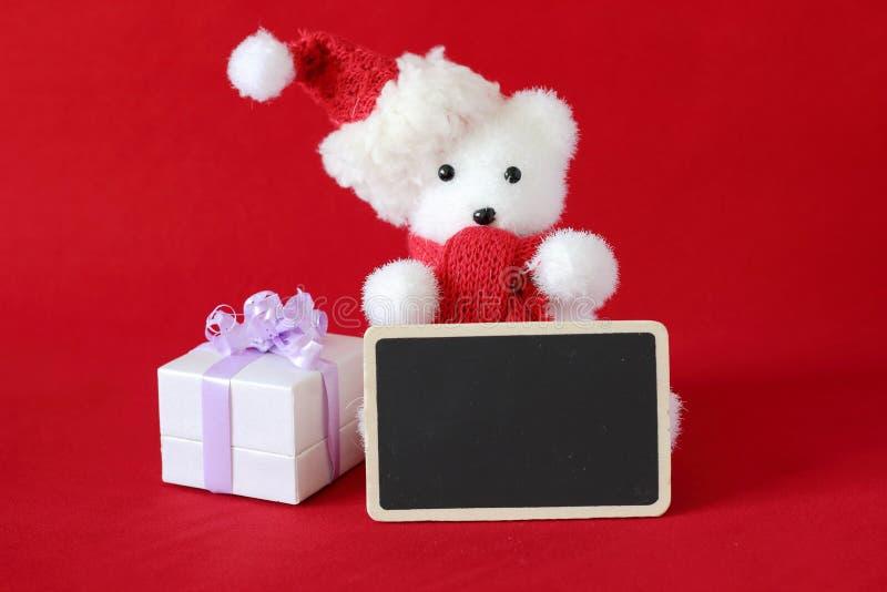 Isbjörnen som bär en hatt, och en röd halsduk för garnering för julparti med ett tomt meddelande kritiserar royaltyfria foton