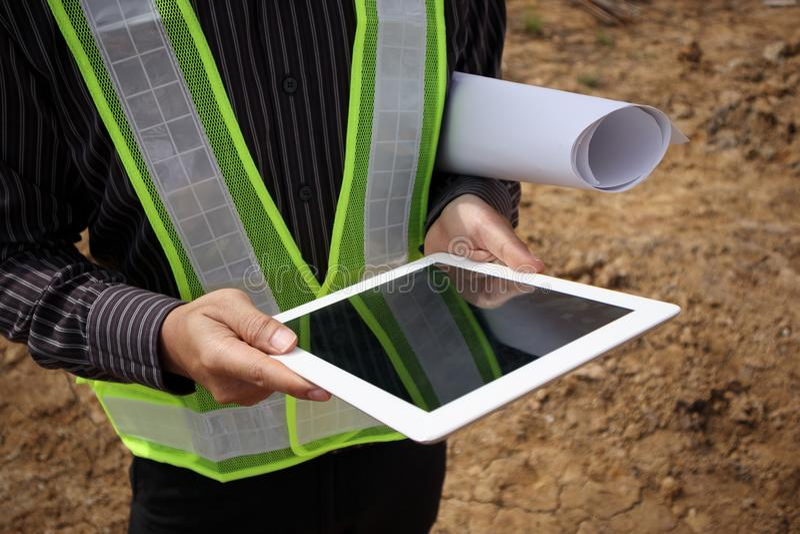 Iscensätta arbetaren som använder minnestavladatoren på byggnadsplatsen royaltyfri fotografi
