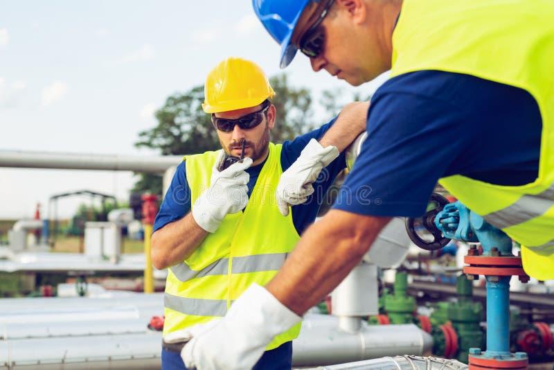 Iscensätta arbete i ett oljeraffinaderi med samtal på den bärbara radion för att kontrollera arbete arkivbilder