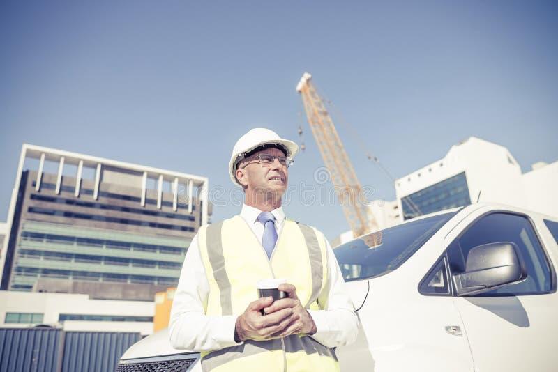 Iscensätta byggmästaren på konstruktionsplats på den soliga dagen med kaffe I royaltyfria bilder