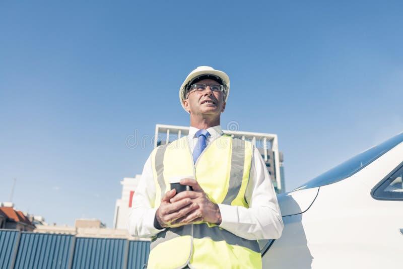 Iscensätta byggmästaren på konstruktionsplats på den soliga dagen med kaffe I royaltyfri foto