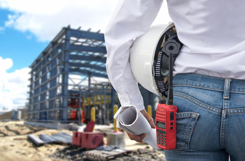 Iscensätta den hållande vita hjälmen för kvinnan och göra en skiss av med radion för arbetarsäkerhetskontroll på kraftverkenergik royaltyfri foto
