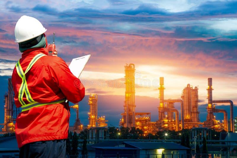 Iscensätta mannen med den vita säkerhetshjälmen som framme står av oljeraffinaderibyggnadsstrukturen i tung petrokemisk bransch,  royaltyfri bild