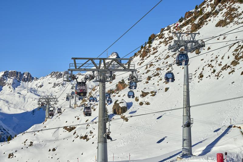 Two links of mono-cable detachable gondolas with high transport capacity lift skiers to the hill top in Tyrol Alps in sunny Decemb. Ischgl, Austria - December 25 stock photo