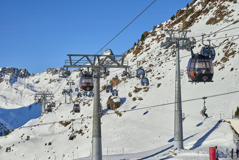 Two links of mono-cable detachable gondolas with high transport capacity lift skiers to the hill top in Tyrol Alps in sunny Decemb royalty free stock image