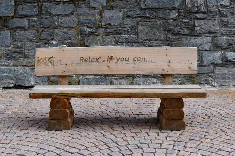 ISCHGL, TYROL, AUSTRIA - AUGUST 26, 2019: Wooden bench with the engraved slogan of the Tyrolean town of Ischgl: Relax. If you can. stock image