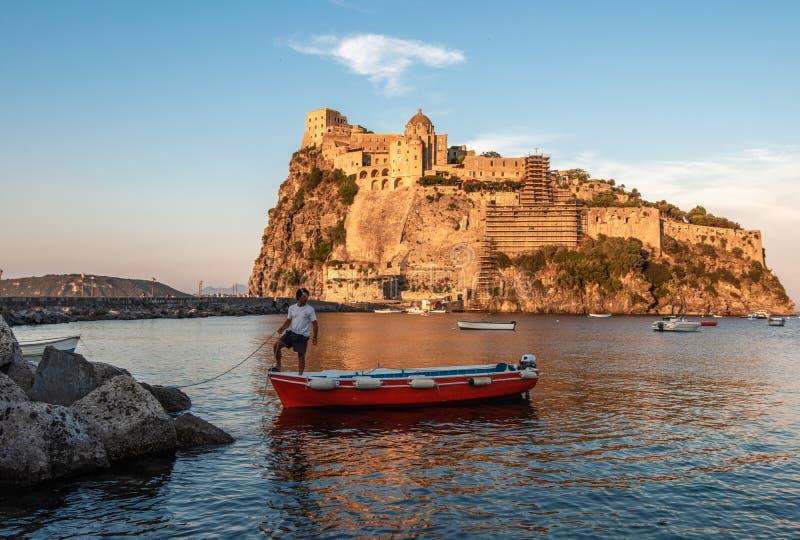 Ischia, Italië 20 Juni, 2017: Boatman met een boot op de achtergrond van het Aragonese-kasteel royalty-vrije stock fotografie