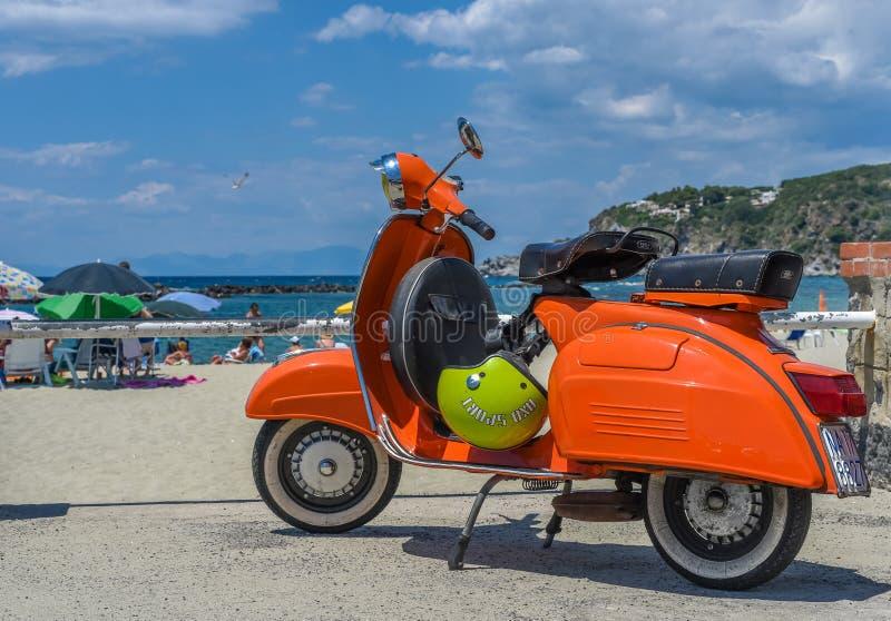 Ischia Italien - Juni 20, 2018: Parkerar den orange Vespasparkcykeln för tappning royaltyfria foton