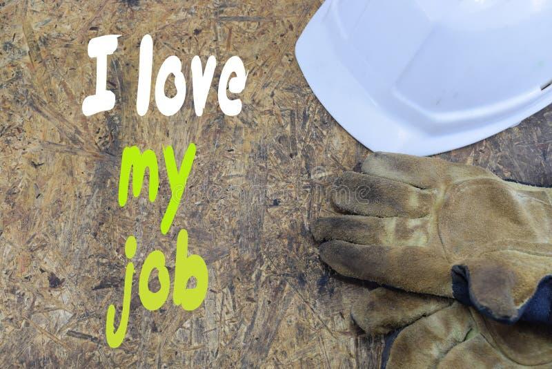 Iscrizione, amo il mio lavoro, contro lo sfondo di un casco bianco di un costruttore con i guanti di lavoro immagine stock libera da diritti
