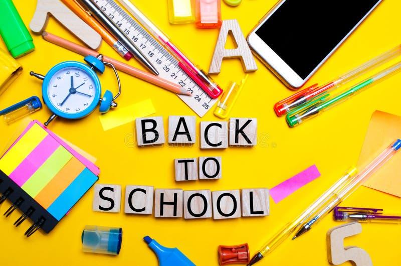 iscrizione dai cubi di legno di nuovo alla scuola Istruisca gli accessori su uno scrittorio su un fondo giallo Concetto di formaz immagine stock libera da diritti
