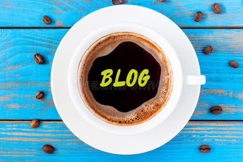 Iscrizione del blog scritta sulla tazza di caffè bianca di mattina nel luogo di lavoro di legno blu Le informazioni sociali di me fotografia stock