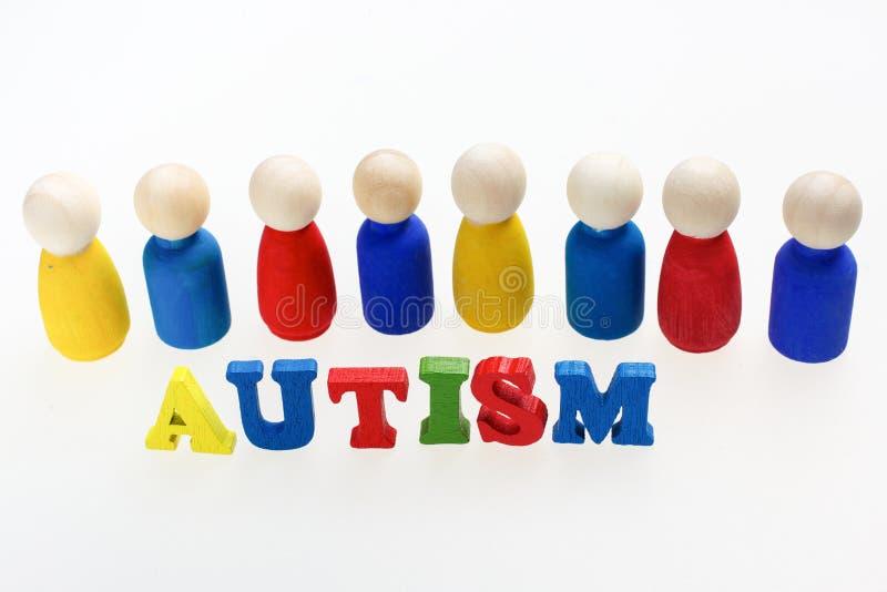 Iscrizione di autismo con le figure e su fondo bianco fotografia stock libera da diritti