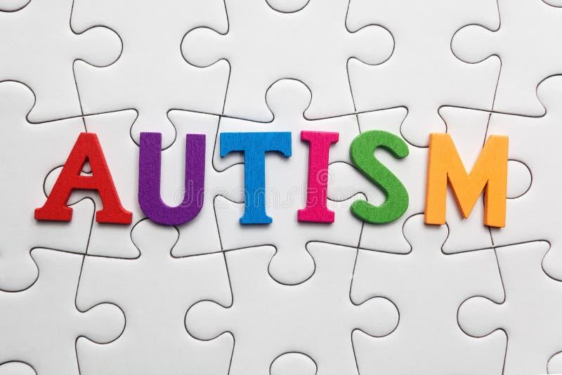 Iscrizione di autismo su un fondo bianco di puzzle immagine stock libera da diritti