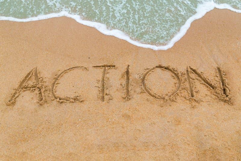 Iscrizione di AZIONE scritta sulla spiaggia sabbiosa con l'avvicinamento dell'onda fotografia stock libera da diritti