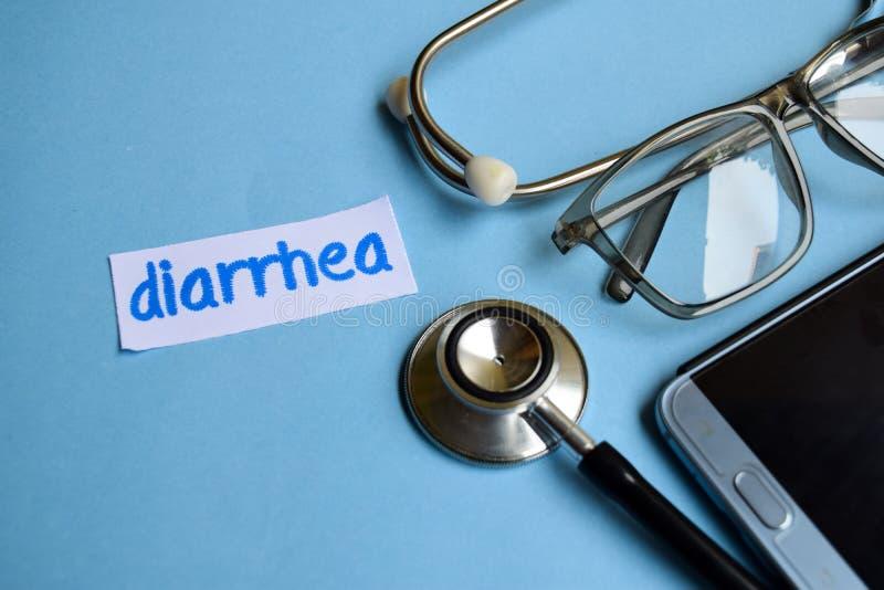 Iscrizione di diarrea con la vista dello stetoscopio, degli occhiali e dello smartphone sui precedenti blu fotografia stock