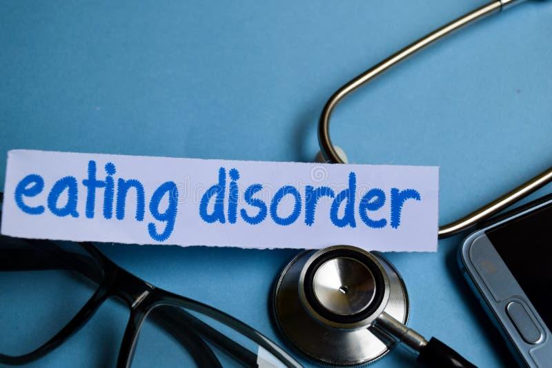 Iscrizione di disordine alimentare con la vista dello stetoscopio, degli occhiali e dello smartphone sui precedenti blu immagini stock