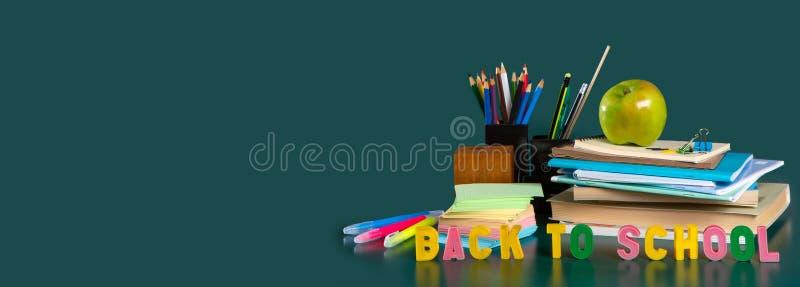 Iscrizione di nuovo alla scuola Natura morta con i rifornimenti di scuola Fondo verde Taccuini, taccuini, pennarelli, colorati fotografie stock libere da diritti