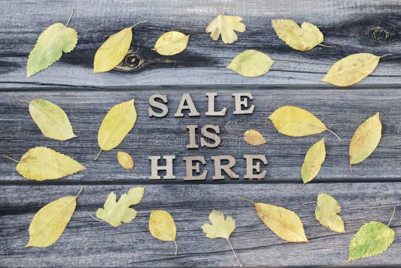 iscrizione La vendita è qui Lettere di legno Pagina di permesso giallo immagini stock