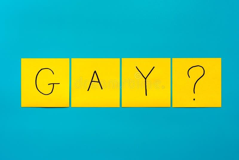 Iscrizione nera scritta a mano gay con il punto interrogativo sugli autoadesivi quadrati gialli su un primo piano blu del fondo,  fotografie stock libere da diritti