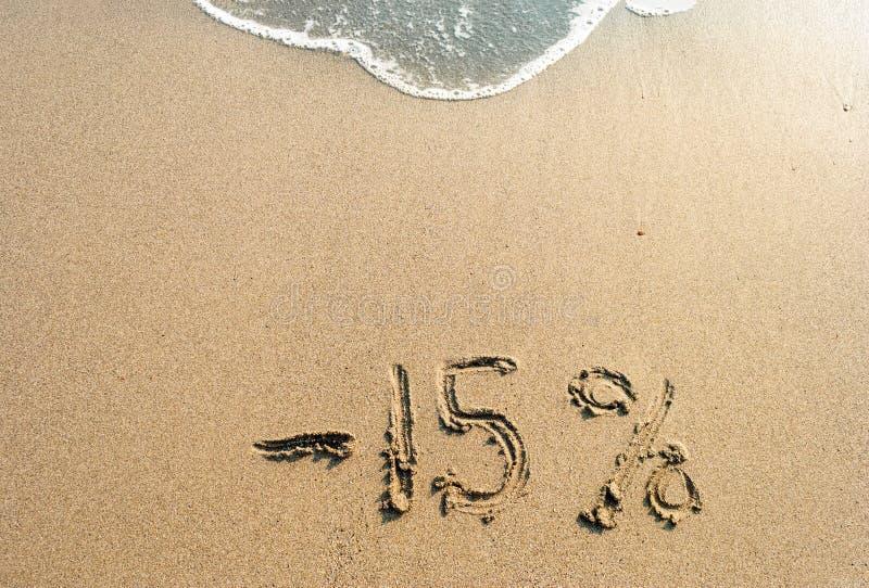 Iscrizione sulla sabbia meno 15 per cento, 15%, onda del mare sulla sabbia con l'iscrizione quindici immagini stock libere da diritti