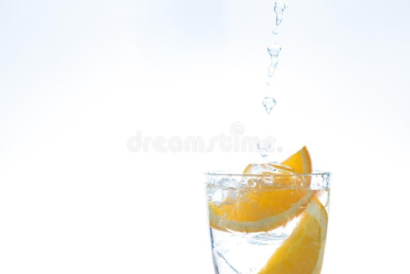 Isdrink med apelsinen och is i studion på en vit bakgrund en ström av vatten häller in i exponeringsglaset royaltyfria bilder
